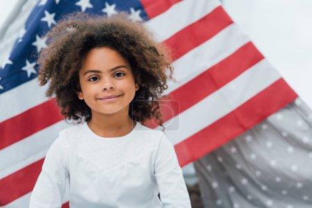 Photo pour Frisé afro-américain gamin regardant caméra près de drapeau de l'Amérique - image libre de droit
