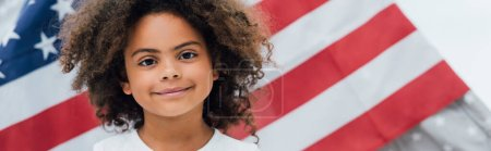 panoramic crop of curly african american kid looking at camera near flag of america