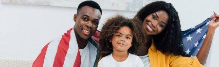 Photo pour Récolte panoramique de la famille afro-américaine recouverte du drapeau de l'Amérique regardant la caméra - image libre de droit