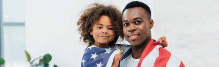 panoramic concept of african american father and daughter covered with flag of america looking at camera