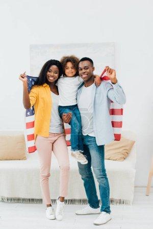 africano americano padre holding en armas niño y bandera de america cerca esposa