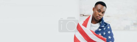 horizontal image of african american man covered with flag of american looking at camera