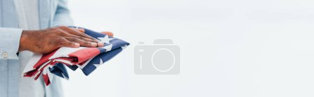 horizontal crop of african american man holding flag of america isolated on white