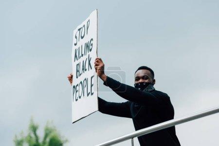 """Afrikanisch-amerikanischer Mann hält Plakat mit der Aufschrift """"Stop killing black people"""" in der Hand"""