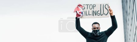 Photo for Horizontal crop of african american man holding flag of america and placard with stop killing us lettering outside - Royalty Free Image