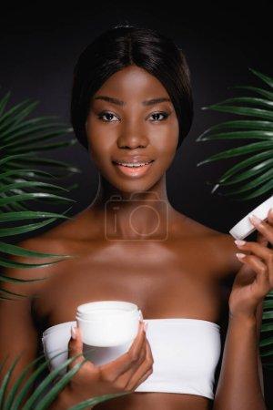Photo pour Afro-américaine avec crème cosmétique près de feuilles de palmier vert isolé sur noir - image libre de droit