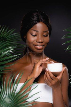 Photo pour Afro-américaine application de crème cosmétique près de feuilles de palmier vert isolé sur noir - image libre de droit
