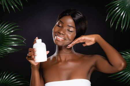 african american woman holding bottle of lotion near green palm leaves isolated on black