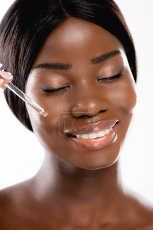 naked african american woman with closed eyes applying serum on face isolated on white