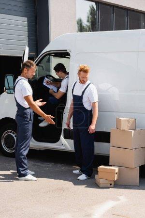 Lader in Uniform zeigt mit der Hand auf Pappkartons in der Nähe von Kollegen und Lastwagen auf der Stadtstraße