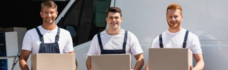 Panoramic orientation of movers in overalls looking at camera while holding cardboard boxes near truck outdoors