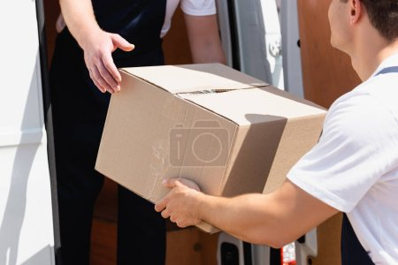 Photo for Cropped view of movers with cardboard box unloading truck outdoors - Royalty Free Image