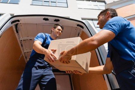 Photo pour Vue à angle bas des chargeuses qui se regardent tout en tenant une boîte en carton dans un camion sur une rue urbaine - image libre de droit