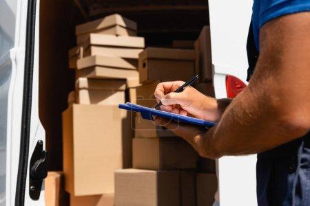 Photo pour Vue recadrée de l'écriture du chargeur sur le presse-papiers à côté des boîtes en carton dans le camion à l'extérieur - image libre de droit