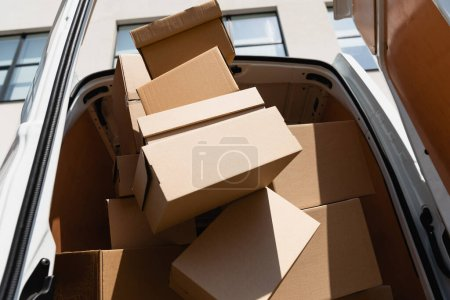 Photo for Low angle view of carton boxes in truck with open doors on urban street - Royalty Free Image