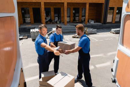 Selective focus of loader with clipboard and pen pointing with hand near colleagues with carton boxes beside truck on urban street