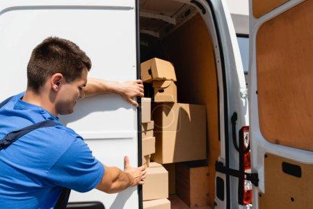 Photo pour Chargeur porte de fermeture de camion avec boîtes en carton à l'extérieur - image libre de droit