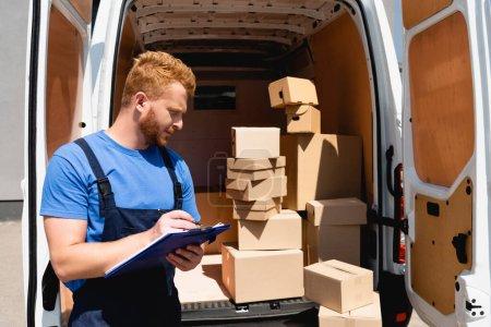 Photo pour Chargeur en salopette tenant presse-papiers près du camion avec des paquets à l'extérieur - image libre de droit