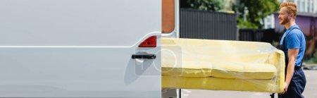 Photo pour Image horizontale du chargeur tenant le canapé près du camion avec des portes ouvertes sur la rue urbaine - image libre de droit