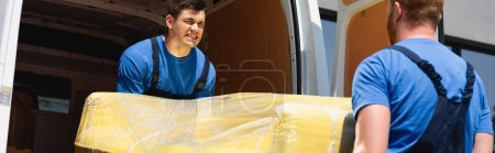 Photo for Panoramic orientation of movers unloading couch in stretch wrap in truck outdoors - Royalty Free Image