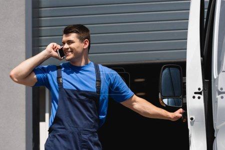 Loader in overalls talking on smartphone near truck on urban street