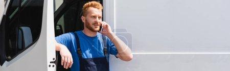 Photo pour Prise de vue panoramique du chargeur en salopette parlant sur smartphone près du camion à l'extérieur - image libre de droit
