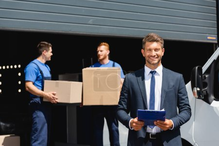 Photo for Selective focus of businessman holding clipboard while movers holding carton boxes near truck and warehouse - Royalty Free Image