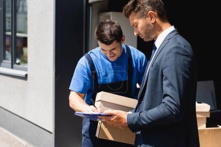 Photo pour Chargeur avec boîtes en carton écrivant sur presse-papiers près d'un homme d'affaires dans une rue urbaine - image libre de droit