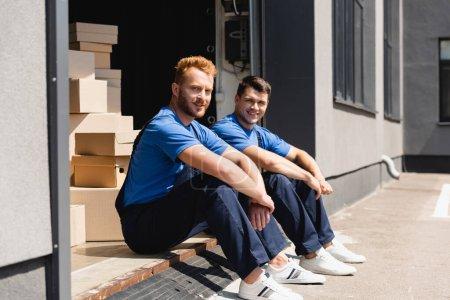 Foto de Enfoque selectivo de cargadores mirando a la cámara mientras están sentados en el almacén al aire libre - Imagen libre de derechos