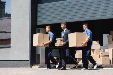 Geschäftsmann hält Kartons in der Hand, während er mit Movern auf der städtischen Straße spaziert