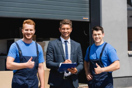 Movers showing thumbs up at camera near businessman writing on clipboard outdoors