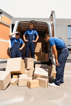 Photo for Pensive movers looking at packages near truck on urban street - Royalty Free Image