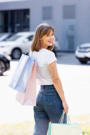 Back view of woman with colorful shopping bags looking at camera on urban street