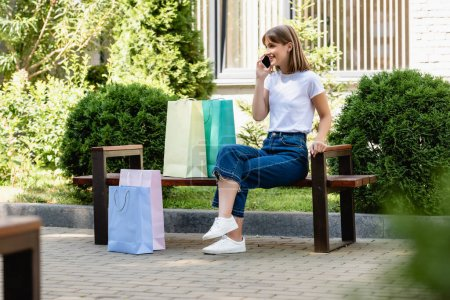 Photo for Selective focus of woman talking on smartphone near shopping bags on bench on urban street - Royalty Free Image
