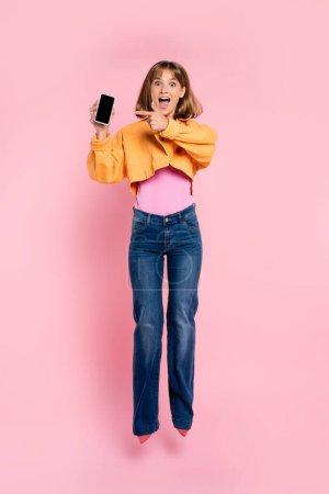Podekscytowana kobieta skacze i wskazuje palcem na smartfona na różowym tle