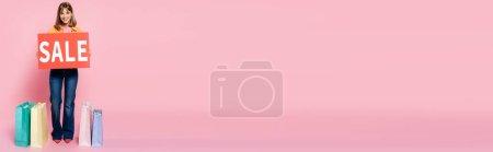 Photo pour Concept horizontal de femme tenant la carte avec le lettrage de vente près des sacs à provisions sur fond rose - image libre de droit