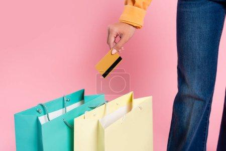 Vue recadrée de la femme tenant la carte de crédit près des sacs à provisions sur fond rose