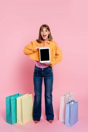 Photo pour Femme excitée en veste jaune tenant tablette numérique près de sacs à provisions colorés sur fond rose - image libre de droit
