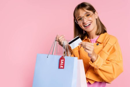 Photo for Young woman in sunglasses holding credit card and shopping bags with sale lettering on price tag on pink background - Royalty Free Image