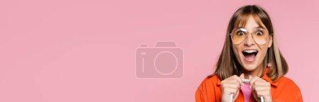 Vue panoramique de femme excitée dans des lunettes de soleil regardant la caméra isolée sur rose