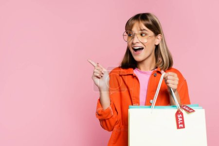 Photo for Young woman pointing with finger while holding shopping bags with sale lettering on pink background - Royalty Free Image