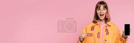 Photo pour Récolte panoramique de femme choquée tenant étiquette de prix avec mot de vente et smartphone isolé sur rose - image libre de droit