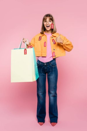 Excited woman holding shopping bags with price tags and showing thumb up on pink background