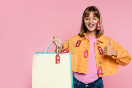 Photo for Woman with closed eyes holding shopping bags with price tags and showing thumb up isolated on pink - Royalty Free Image