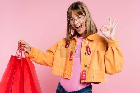 Photo pour Femme avec des étiquettes de prix sur veste holing sacs à provisions rouges et montrant geste correct sur fond rose - image libre de droit