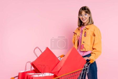 Photo pour Jeune femme en lunettes de soleil avec des étiquettes de prix sur la veste debout près du chariot avec des sacs à provisions sur fond rose - image libre de droit