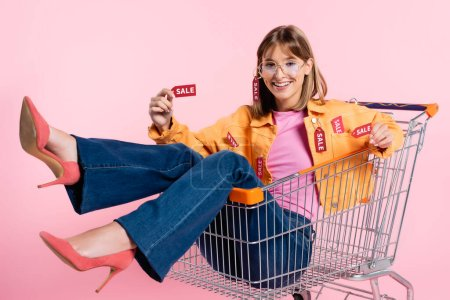 Selective focus of young woman showing price tags with sale lettering at camera in shopping trolley on pink background