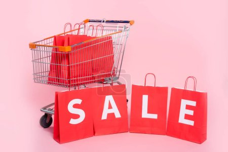 Photo pour Vente de lettrage sur sacs rouges près du chariot sur fond rose - image libre de droit