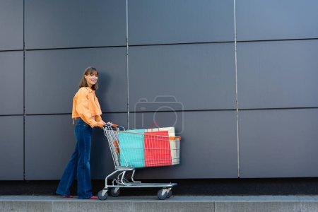 Junge Frau läuft mit Einkaufstüten in Einkaufswagen und baut im Freien