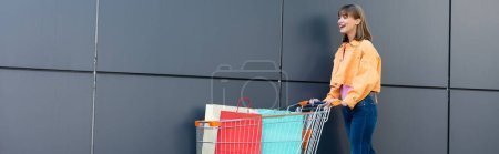 Photo for Panoramic concept of excited woman walking near cart with shopping bags and facade of building - Royalty Free Image